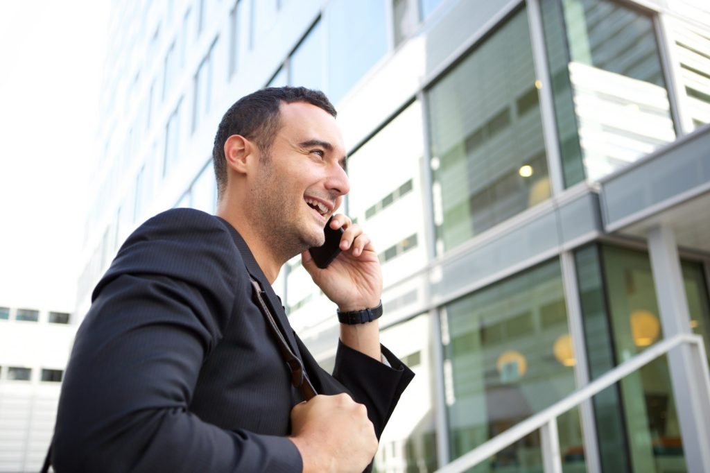 businessman talking on mobile phone by city building